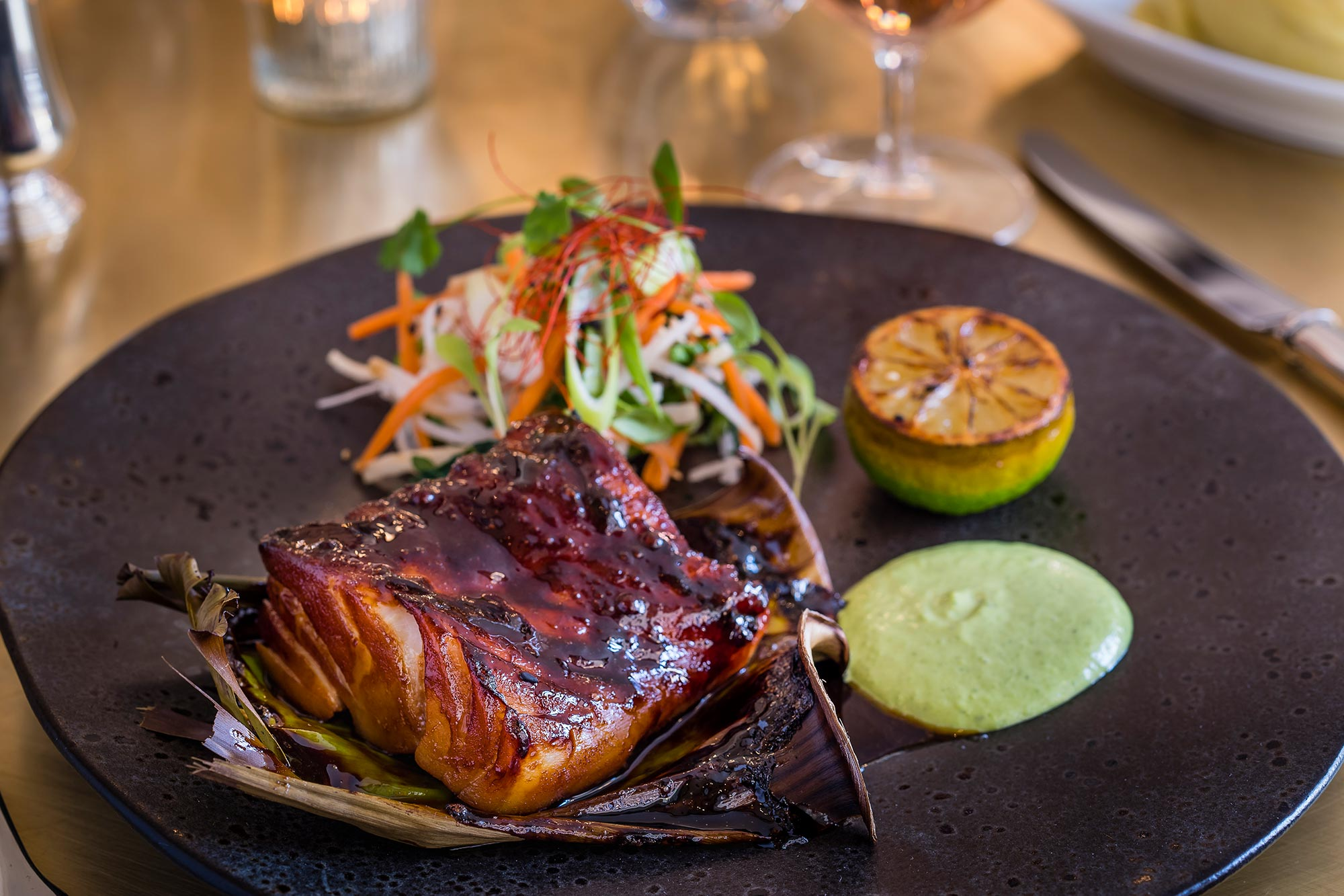 The Ivy Cobham Brasserie - Blackened Cod, banana leaf with a miso glaze, spring onion, and salad - The Ivy Cobham Brasserie