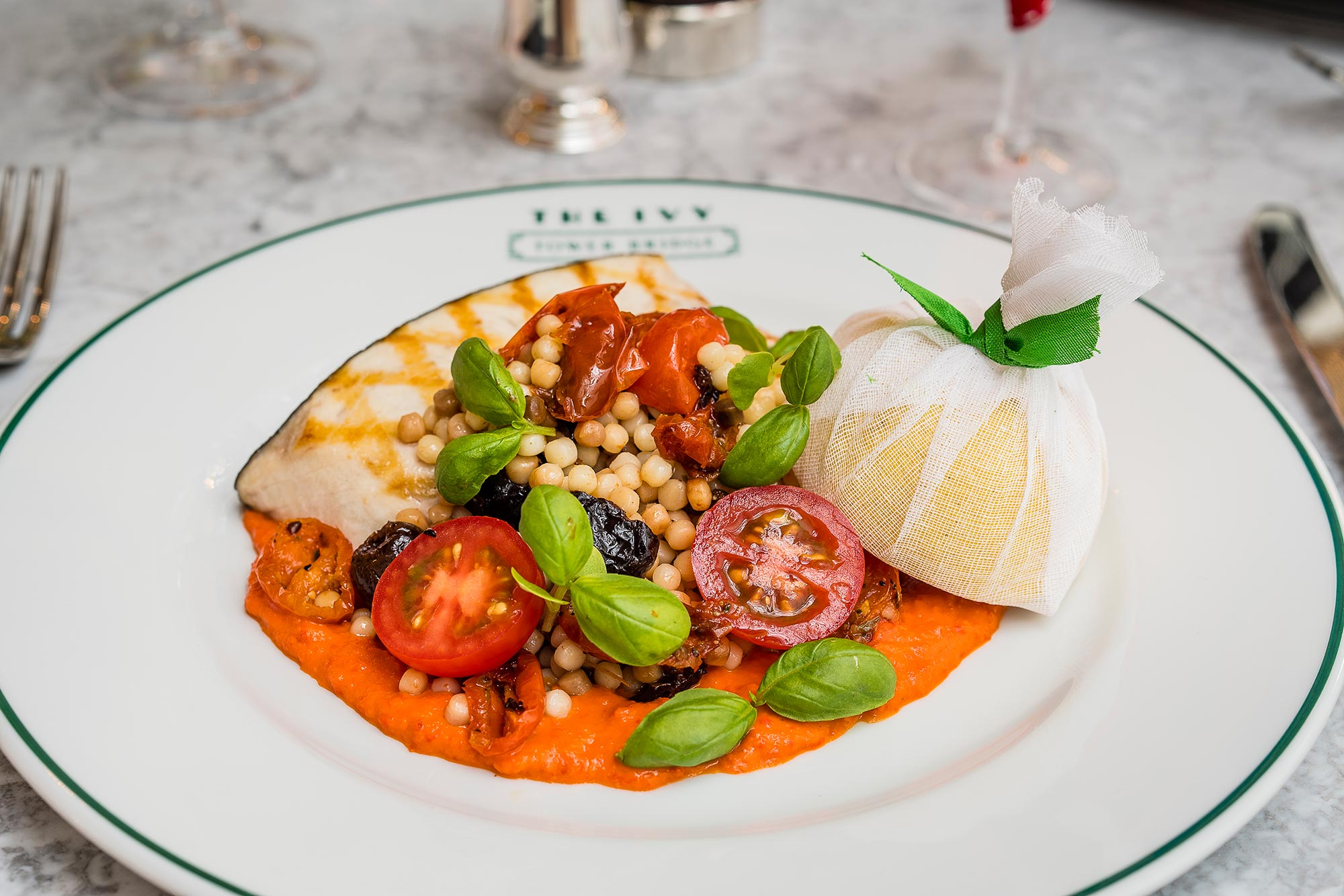 Swordfish, red pepper sauce, cherry tomatoes, fregola, pesto at The Ivy Market Grill - The Ivy Market Grill